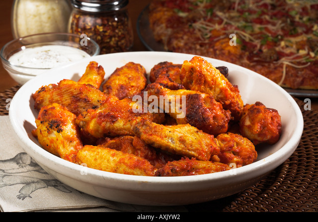 fried baked food seasoned chicken wings in white bowl next to pizza cheese cream sauce spice on mat yellow brown - Stock Image