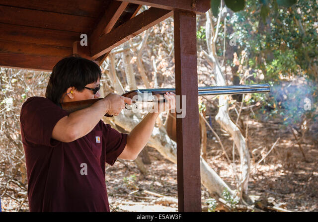 Asian American man shooting clays with smoke coming out of his shotgun - Stock Image