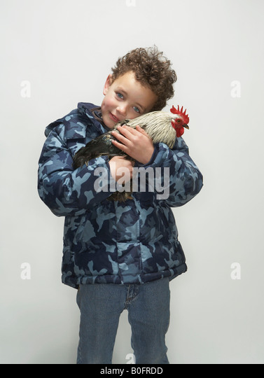 Boy holding cockerel - Stock Image