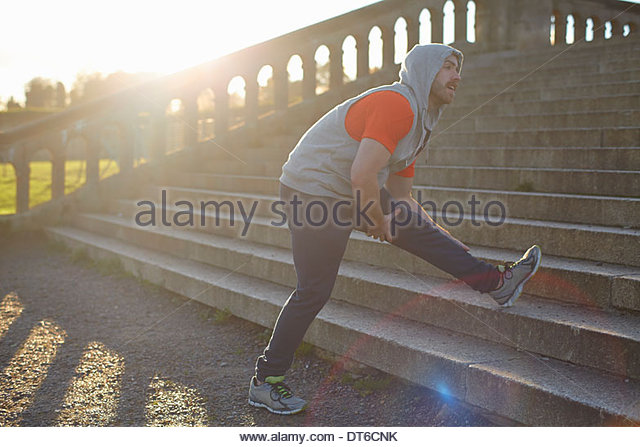 Young man stretching leg on step - Stock Image