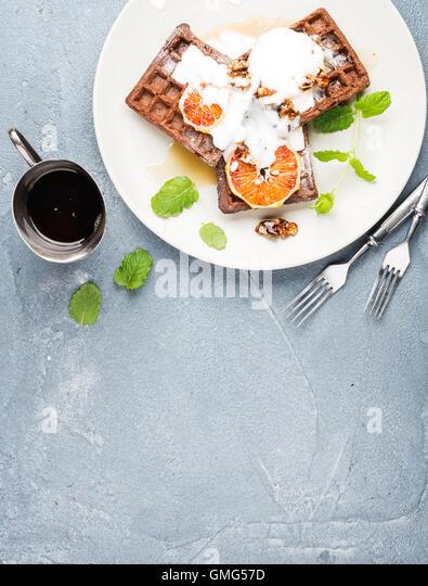 Belgian soft waffles with blood orange, cream, marple syrup and mint on white plates - Stock Image
