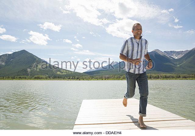 Mature man running on dock - Stock Image
