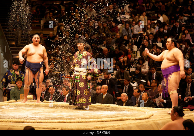 Some sumo fighters throwing salt before a fight at the Kokugikan stadium, Tokyo, Japan, Asia - Stock Image