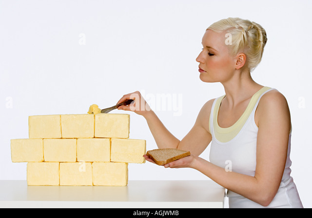 Young woman scraping butter - Stock Image
