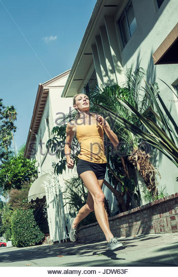 Young woman jogging in street, low angle view - Stock-Bilder