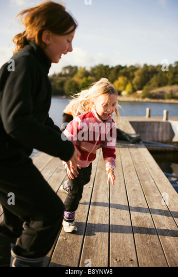 Two girls playing on a jetty Stockholm archipelago Sweden. - Stock Image