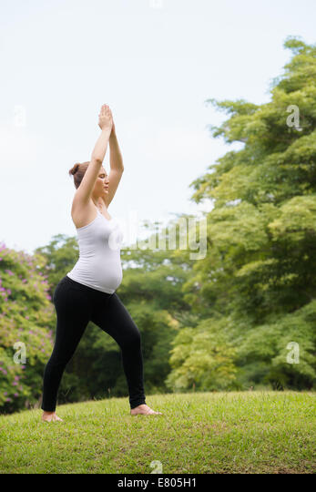 pregnant woman doing yoga in park - Stock Image