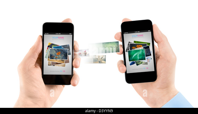 Two hands holding mobile smartphones while transferring pictures from one to another. - Stock-Bilder