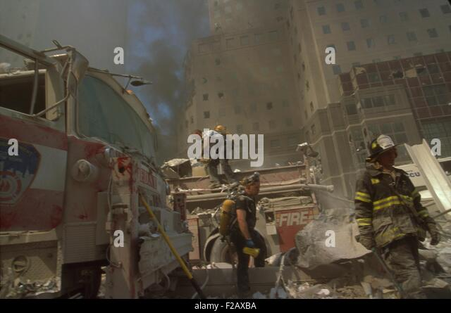 Fire fighters amid debris following September 11th terrorist attack on World Trade Center. In the background are - Stock-Bilder