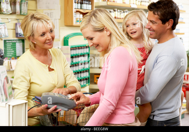 Female sales assistant in health food store - Stock Image
