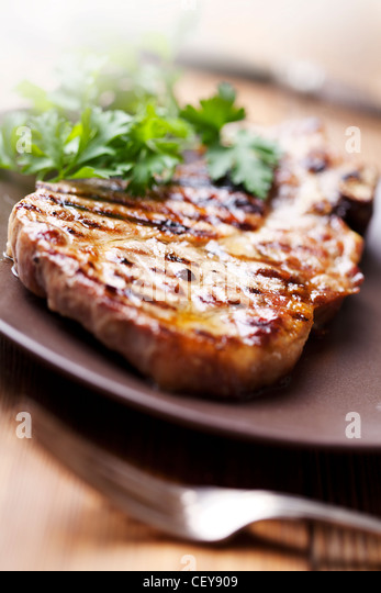 juicy grilled pork chop (neck cut) with greens - Stock Image