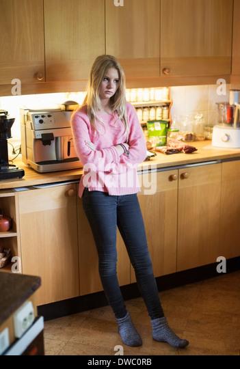 Full length of sad teenage girl standing in kitchen - Stock Image
