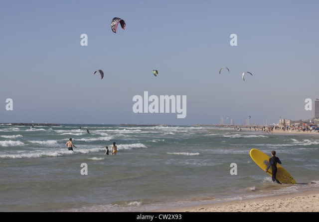 Surfer entering the water with kite-surfers and swimmers in the background, Tel Aviv, Israel - Stock Image