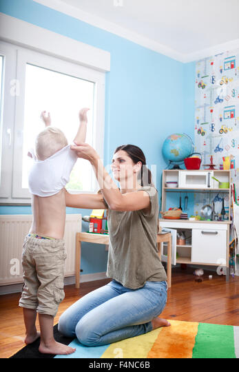 Woman undressing his little son at children's room - Stock Image