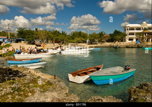 Tourists and tour boats Bayahibe fishing village gateway for day trips to Isla Saona Dominican Republic southeast - Stock Image