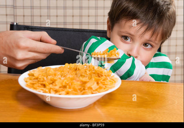 Close-up of a boy refusing corn flakes - Stock Image