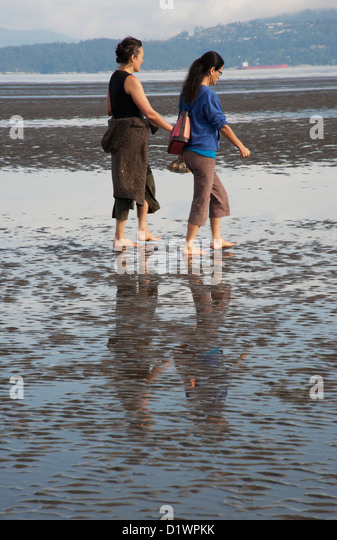 Two woman walking along the beach when the tide is out, Vancouver, British Columbia, Canada - Stock Image