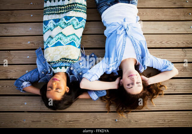 Two women lying on back with eyes closed - Stock Image