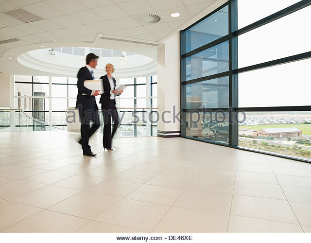 Business people walking through office lobby - Stock-Bilder