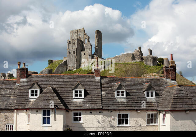 The ancient and medieval remains of Corfe Castle in Dorset on a hill behind houses - Stock Image