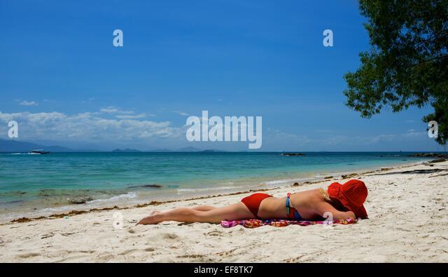 Malaysia, Woman relaxing on beach - Stock Image