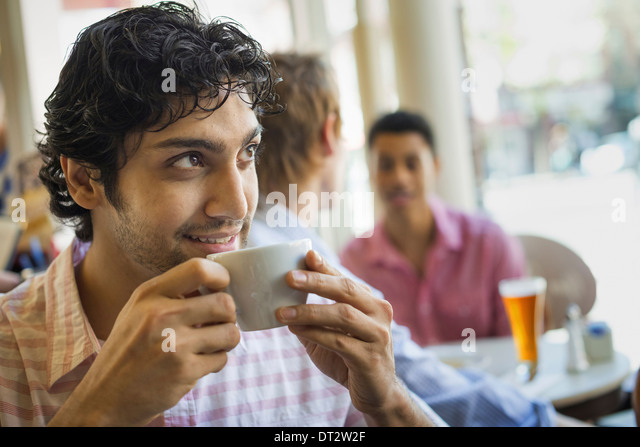 Urban Lifestyle Three young men around a table in a cafe One man taking a drink from a cup of coffee - Stock Image