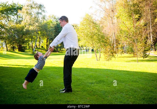 Man spinning around a little boy - Stock Image