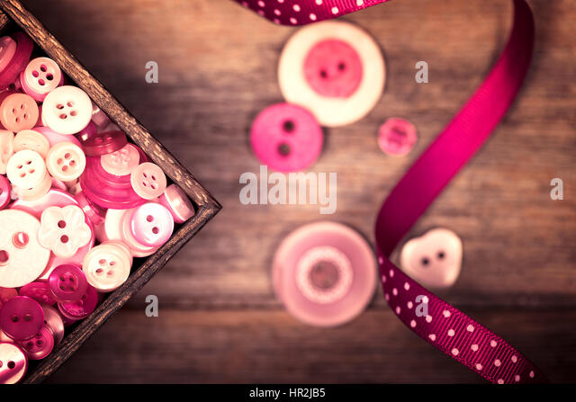 A close up of a box of pink and white buttons, with a pink polka dot ribbon alongside. Filtered to have a faded - Stock-Bilder