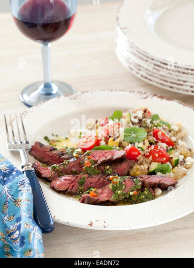 Grilled Beef and Couscous salad with glass of red wine. - Stock Image