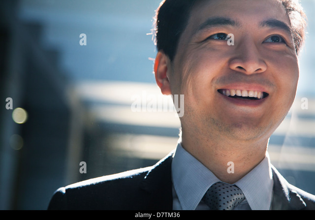 Portrait of smiling businessman in a parking garage - Stock Image