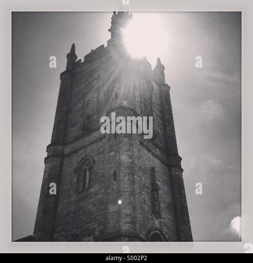 Sunburst over village church, Cerne Abbas, Dorset, England - Stock Image