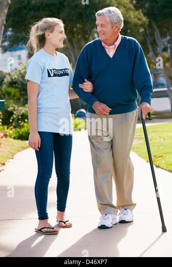 Teenage Volunteer Helping Senior Man Walking Through Park - Stock Image