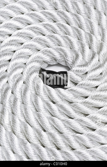Close-up of a white rope curled up and filling the frame - Stock Image