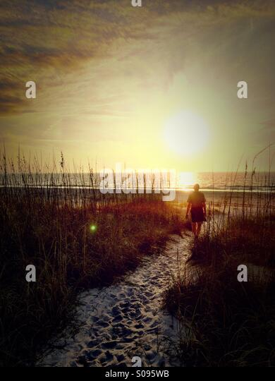 Man walking towards Gulf of Mexico, St Petes Beach, Florida - Stock Image