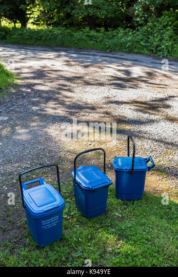 Blue plastic food waste bins awaiting collection on a narrow country road in Monmouthshire, Wales. - Stock Image