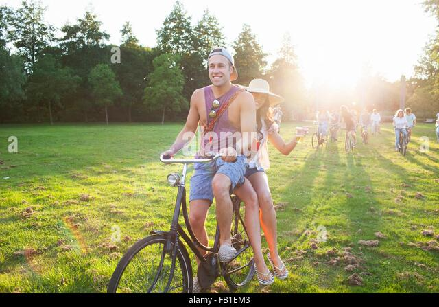 Crowd of partygoing adults arriving on cycles to sunset park party - Stock Image