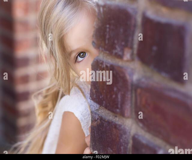 Girl peeking around a brick wall - Stock Image