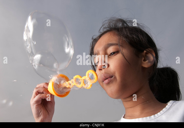 Young child blowing bubbles - Stock-Bilder