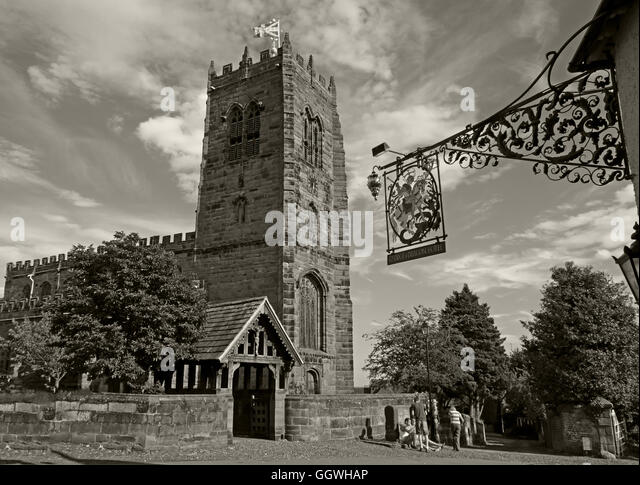 George and Dragon wrought iron sign and St Marys Church,Great Budworth,Cheshire,England, UK - Monochrome Sepia - Stock Image