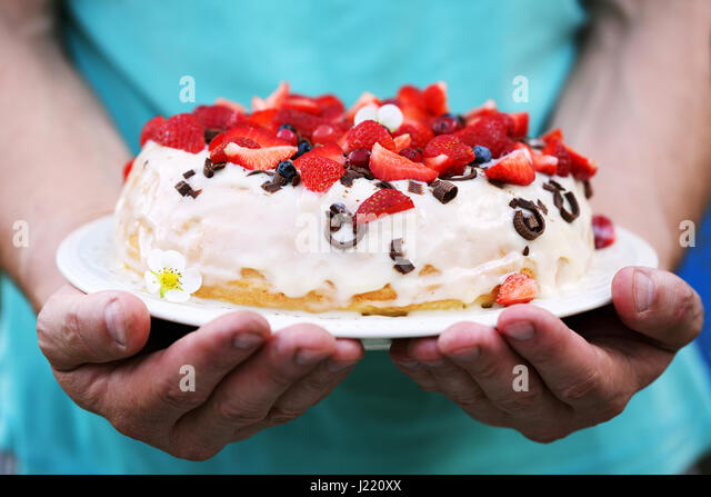 Cake in men's hands - Stock Image