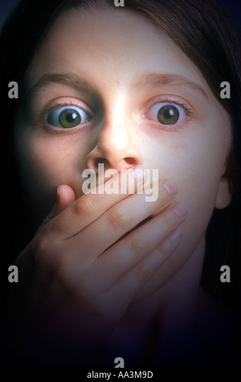 young girl face giving look of surprise with hand in front of mouth - Stock-Bilder
