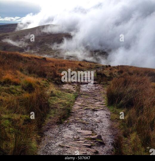 A mountain path through mist and cloud in the Brecon Beacons National Park in Wales - Stock Image
