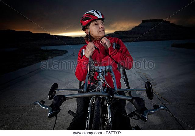 Paraplegic woman adjusting her helmet safety strap, Colorado, America, USA - Stock Image