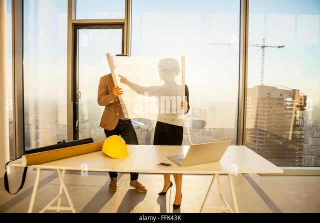 Two architects in office examining blueprint - Stock Image