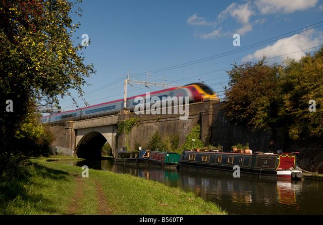 Intercity train flies over a canal bridge - Stock-Bilder