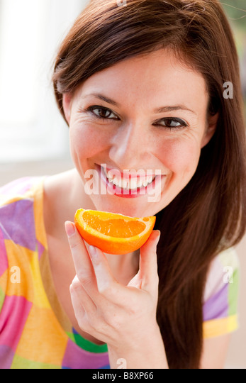 Woman eating a Orange segment - Stock Image