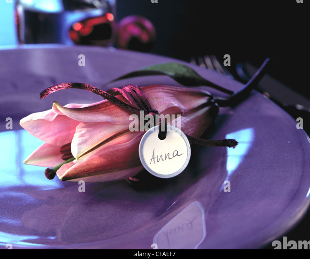 Still: Pink lily with name plates as table reservation - Stock Image