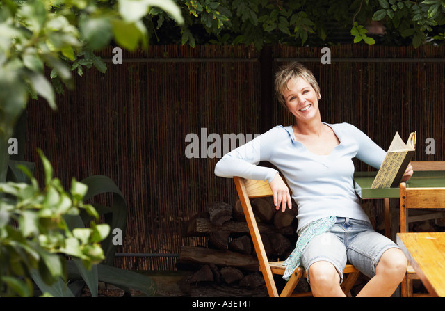 Portrait of a mature woman holding a book and smiling - Stock Image