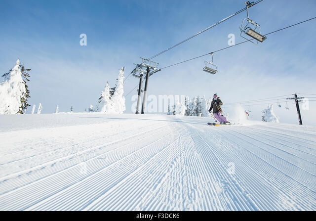 Mid-adult woman on ski slope under cable car - Stock Image