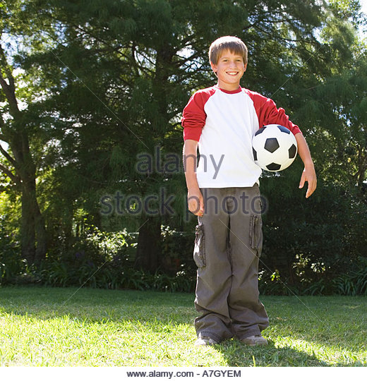 Young boy holding a football in a garden - Stock Image